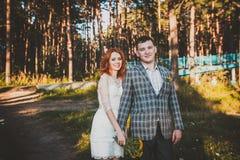 La sposa e lo sposo che posano nella foresta Fotografie Stock Libere da Diritti