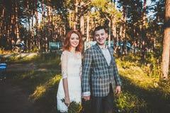 La sposa e lo sposo che posano nella foresta Immagini Stock Libere da Diritti