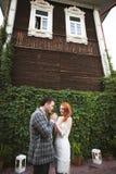 La sposa e lo sposo che posano vicino ad un recinto verde e ad una vecchia casa Fotografie Stock