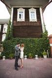 La sposa e lo sposo che posano vicino ad un recinto verde e ad una vecchia casa Immagine Stock