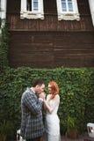 La sposa e lo sposo che posano vicino ad un recinto verde e ad una vecchia casa Immagini Stock Libere da Diritti