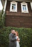 La sposa e lo sposo che posano vicino ad un recinto verde e ad una vecchia casa Fotografia Stock Libera da Diritti