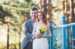 La sposa e lo sposo che posano vicino al ponte blu Fotografia Stock Libera da Diritti