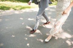 La sposa e lo sposo che si allontanano di estate parcheggiano all'aperto Immagine Stock