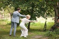 La sposa e lo sposo che si allontanano di estate parcheggiano all'aperto Fotografia Stock