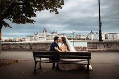 La sposa e lo sposo che si siedono sul banco vicino al fiume nella vecchia citt? Sarchiatura a Budapest fotografia stock libera da diritti
