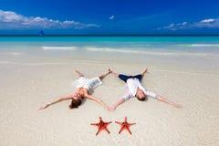 La sposa e lo sposo che si trovano sulla spiaggia puntellano con due stelle marine Fotografia Stock