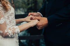 La sposa e lo sposo/coppia sta tenendosi per mano Immagini Stock