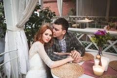 La sposa e lo sposo hanno cena romantica in caffè della via Fotografie Stock
