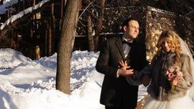 La sposa e lo sposo sono su una strada nevosa stock footage