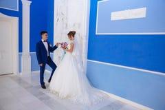 La sposa e lo sposo stanno aspettando l'inizio del loro matrimonio Un uomo in un vestito blu con attenzione giudica il suo caro v fotografia stock