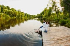 La sposa e lo sposo stanno sedendo su un pilastro di legno vicino allo stagno Immagini Stock Libere da Diritti