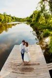 La sposa e lo sposo stanno stando su un pilastro di legno vicino allo stagno Fotografie Stock Libere da Diritti