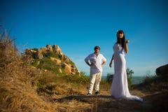 La sposa e lo sposo stanno sui precedenti delle montagne e del cielo fotografia stock