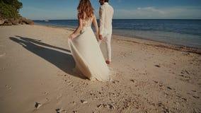 La sposa e lo sposo vanno a piedi nudi su una spiaggia sabbiosa accanto all'oceano blu Stanno tenendo per mano felice insieme stock footage