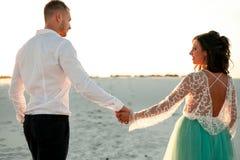 La sposa e lo sposo vanno sulla sabbia in deserto, si tengono per mano ed esaminano il eac Immagine Stock