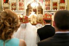 La sposa ed il fidanzato stanno in corone nella parte anteriore dell'altare della chiesa Fotografia Stock