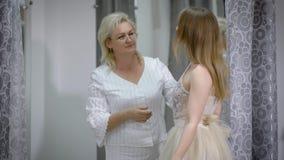 La sposa felice è stante e misura il vestito in atelier con l'assistente di nozze La giovane donna con il sarto da donna sta face stock footage