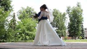 La sposa felice e lo sposo alla moda sorridenti che camminano di estate si inverdiscono il parco con il mazzo dei fiori, del danc stock footage