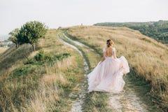 La sposa funziona sugli ascensori della strada della collina si veste fotografie stock libere da diritti