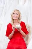 La sposa futura mangia meditatamente la torta di cerimonia nuziale Fotografia Stock Libera da Diritti