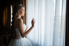 La sposa guarda dalla finestra, giorno delle nozze Fotografia Stock Libera da Diritti