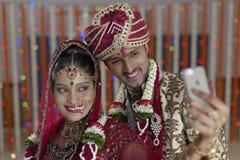 La sposa indù indiana & governa un auto sorridente felice della fucilazione delle coppie con il cellulare. Fotografie Stock