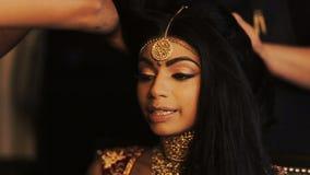 La sposa indiana di fascino tiene le sue dita delicate dietro le sue tempie mentre le donne ottengono lei i capelli pronti