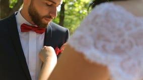 La sposa mette il fazzoletto nella tasca del vestito dello sposo archivi video