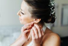 La sposa mette sopra gli orecchini Immagine Stock Libera da Diritti