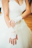 La sposa mette sopra i guanti di nozze Fotografia Stock