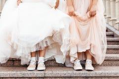 La sposa mostra le scarpe, ragazzo in scarpe da tennis immagini stock libere da diritti