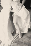 La sposa mostra una giarrettiera del pizzo che aumenta su un vestito da sposa Fotografia Stock