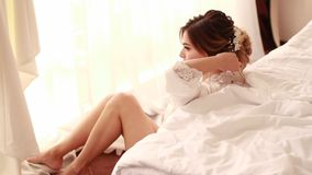 La sposa nel peignoir si siede e raddrizza la sua acconciatura stock footage