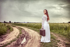 La sposa offensiva che va con una vecchia valigia Immagine Stock Libera da Diritti