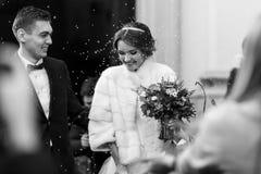 La sposa sembra lanciante sotto la pioggia di riso dopo la cerimonia Fotografia Stock Libera da Diritti