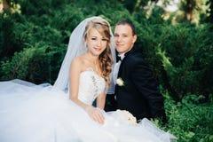 La sposa si siede insieme allo sposo sul parco dell'erba verde Immagini Stock Libere da Diritti