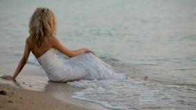 La sposa si siede sulla spiaggia stock footage