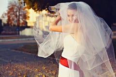 La sposa sorridente gioca con un velo nei raggi del sole di sera Fotografia Stock