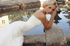 La sposa splendida con capelli biondi indossa il vestito lussuoso e gli accessori Fotografie Stock