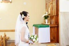 La sposa sta prima dell'altare nella chiesa Immagine Stock Libera da Diritti