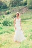La sposa sta su un fondo di erba e delle montagne fotografia stock