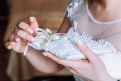 La sposa sta tenendo un cuscino con le fedi nuziali Fotografia Stock Libera da Diritti