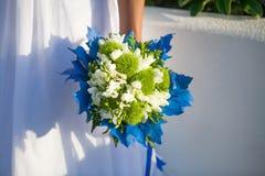 La sposa tiene il mazzo di nozze in colori bianchi e verdi e decorazione blu fotografia stock