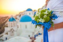 La sposa tiene il mazzo di nozze nei colori bianchi e verdi e decorazione blu contro il contesto del tramonto sopra Santorini, Gr fotografia stock