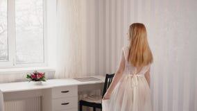 La sposa in un peignoir guarda e tocca un vestito da sposa stock footage