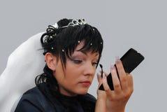 La sposa in un velo di bianco dipinge i suoi cigli prima del weddin fotografie stock libere da diritti