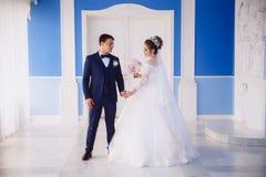 La sposa in un vestito da sposa elegante con ricamo ed in un mazzo delle peonie in sua mano va alla grande porta bianca e immagini stock