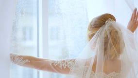 La sposa va alla finestra ed ha spinto la tenda video d archivio