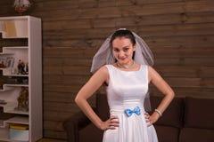 La sposa in velo ed il bianco si vestono con la posa blu dell'arco immagini stock libere da diritti